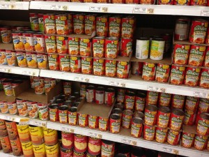Assortment of Chef Boyardee products in the canned goods aisle in a typical grocery store.