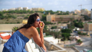 happy-woman-eating-apple-on-the-terrace_V1GrmfXi.mov.00_00_20_20.Still001